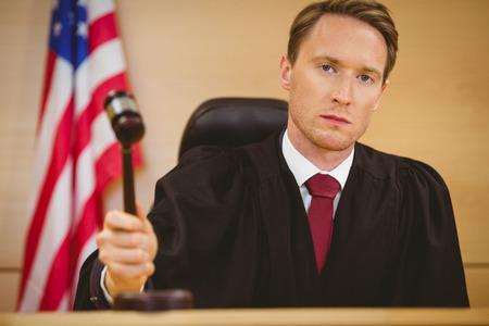 martillo juez: Juez serio a punto de golpear el martillo en el bloque de sonar en la sala del tribunal