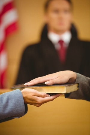 swearing: Witness swearing on the bible telling the truth in the court room Stock Photo