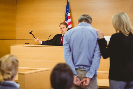 court room: Judge about to bang gavel on sounding block in the court room