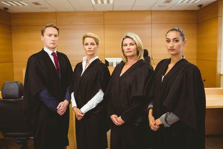 court room: Four serious judges standing while wearing robes in the court room
