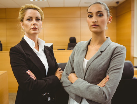 trial indoor: Two serious lawyers standing with arms crossed in the court room Stock Photo