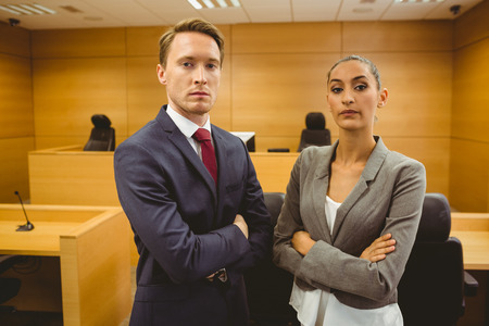 unsmiling: Unsmiling lawyers looking at camera crossed arms in the court room