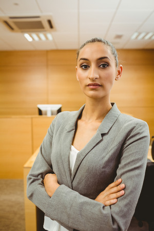 unsmiling: Unsmiling lawyer looking at camera crossed arms in the court room