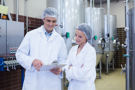 Scientist speaking to his colleague holding clipboard in the factory