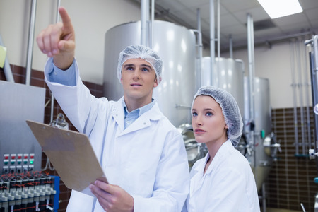 colleague: Man pointing at something to his colleague in the factory