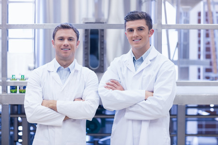 microbrewery: Scientist team smiling at camera with arms crossed in the factory