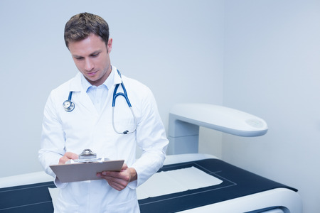 noting: Doctor noting something on his clipboard at medical office