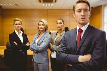 법정 방에서 팔을 들고 서있는 중대한 변호사가 건넜다.