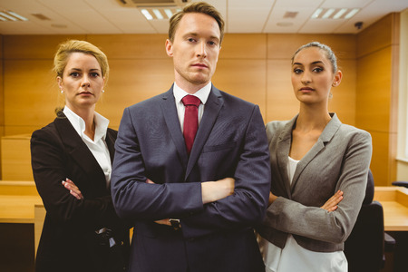 Three serious lawyers standing with arms crossed in the court room