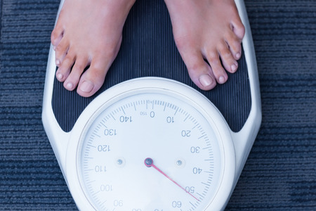 losing weight: Close up of a woman standing on the scales in hospital