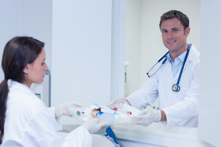 sample tray: Doctor giving tray with blood sample to his colleague in hospital