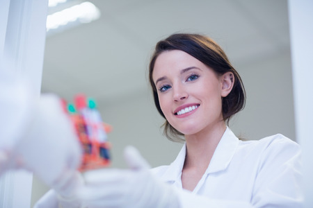 biologist: Young female biologist smiling at the camera in hospital