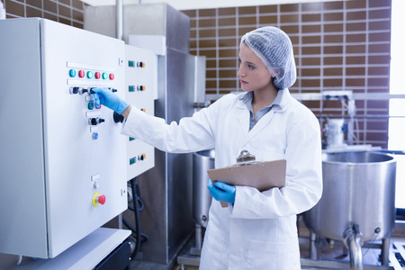 biologist: Focused biologist holding clipboard and pressing on button in the factory
