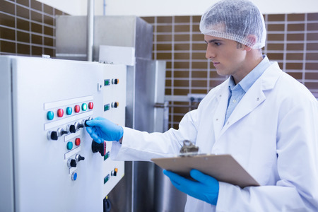 biologist: Focused biologist using the machine in the factory
