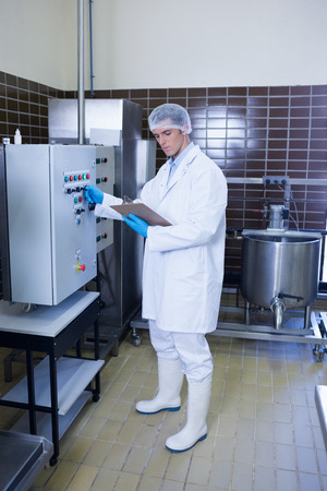 biologist: Focused biologist with safety gloves holding clipboard in the factory