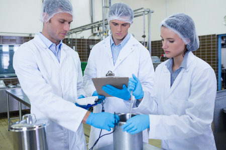 factory: Man writing on clipboard while colleagues testing product in the factory