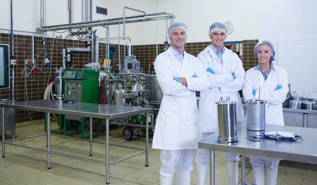 biologist: Biologist team with arms crossed smiling at camera in the factory