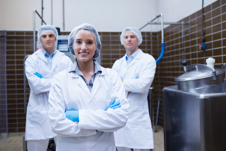 food industry: Biologist team standing smiling with arms crossed in the factory Stock Photo