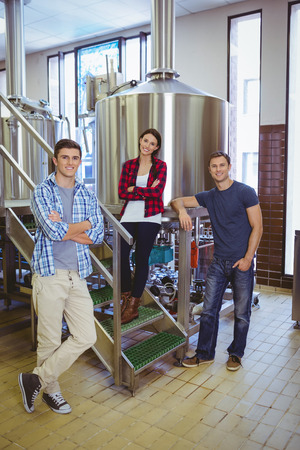 microbrewery: Happy hipster smiling at camera together in the factory Stock Photo