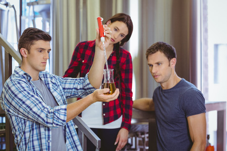 microbrewery: Man pouring beer into the beaker with a pipette in the factory Stock Photo