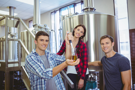 pouring beer: Man pouring beer into the beaker with a pipette in the factory Stock Photo