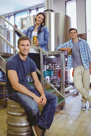 microbrewery: Man siting on keg and his colleague holding a glass of beer in the factory