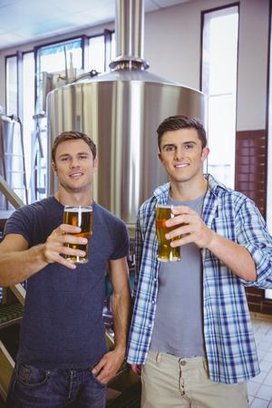 microbrewery: Young men holding a pint of beer smiling at camera in the factory Stock Photo
