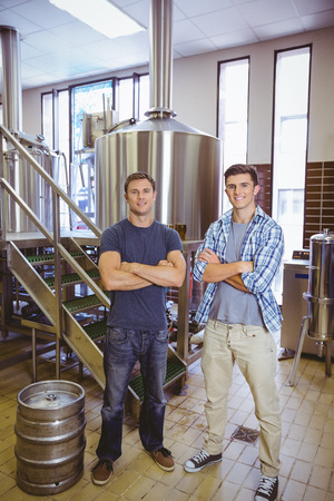 microbrewery: Young men with arms crossed smiling at camera in the factory Stock Photo