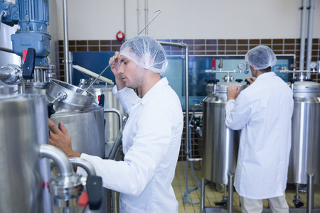 lab coat: Scientists wearing lab coat and hair net in the factory Stock Photo