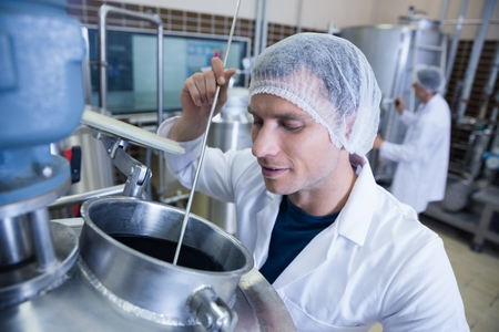 brewer: Scientist using brewer in the container in the factory