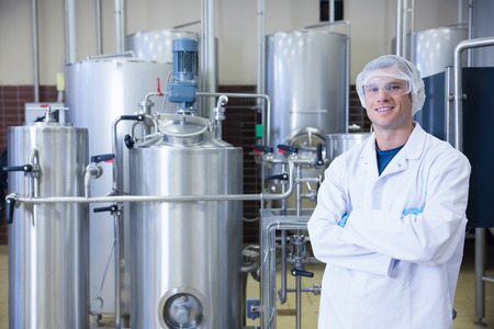 microbrewery: Scientist with arms crossed wearing protective glasses in the factory Stock Photo