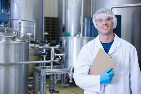 food industry: Smiling scientist looking at camera holding a clipboard in the factory