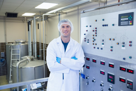 microbrewery: Portrait of a smiling scientist with arms crossed in the factory