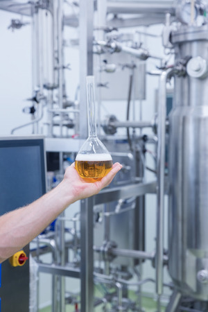 microbrewery: Hand showing a beaker of beer in the factory Stock Photo