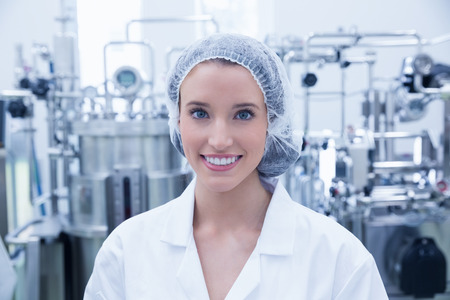 microbrewery: Portrait of a smiling scientist wearing hair net in the factory Stock Photo