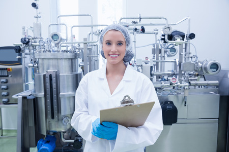 Portrait of a smiling scientist holding a clipboard in the factory