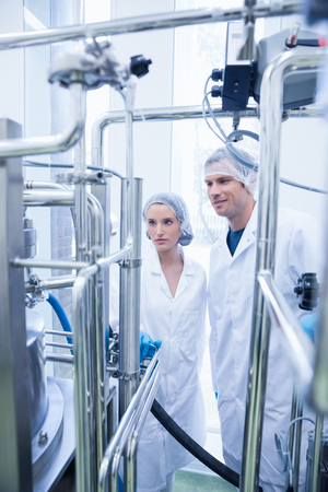 microbrewery: Smiling scientist with colleague looking metal gauge in the factory Stock Photo
