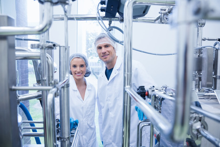 young plant: Scientist team behind metal gauge looking at camera in the factory