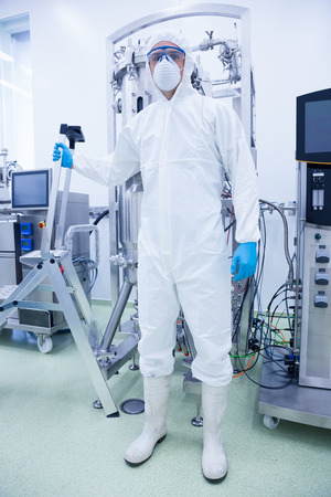 microbrewery: Scientist in protective suit holding ladder in the factory