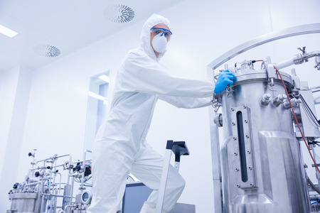 microbrewery: Scientist standing on ladder looking at the camera in the factory Stock Photo