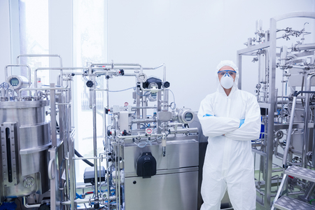 protective suit: Scientist in protective suit standing with arms crossed in the factory