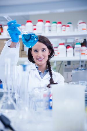 young caucasian: Chemist raising beaker of blue liquid in lab Stock Photo