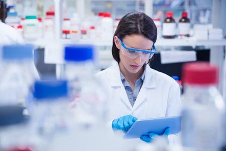 화학자 안전 안경을 착용하고 실험실에서 태블릿 PC를 사용하여 스톡 콘텐츠