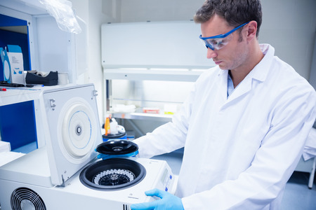 centrifuge: Chemist wearing safety glasses and using a centrifuge in lab Stock Photo