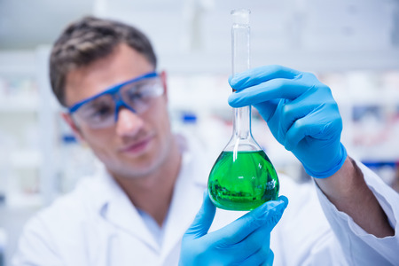 Chemist holding up beaker of green chemical in the laboratory Stock Photo