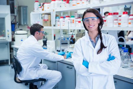 Retrato de un químico sonriendo con los brazos cruzados en el laboratorio
