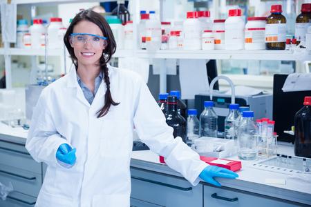 Portret van een lachende chemicus leunend tegen een bureau in het laboratorium Stockfoto