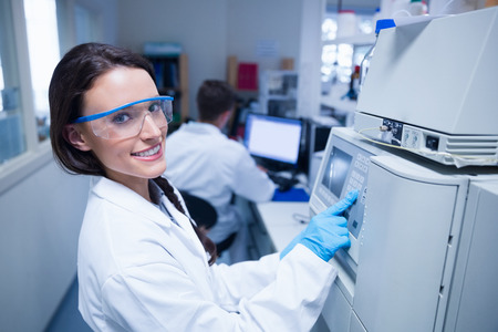 laboratory technician: Smiling young chemist using the machine in the laboratory