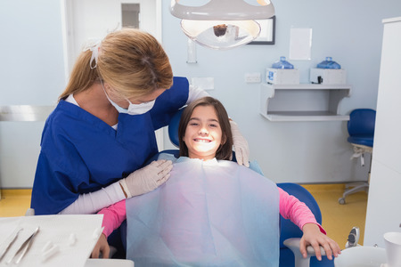 pediatric: Pediatric dentist examining her smiling young patient in dental clinic