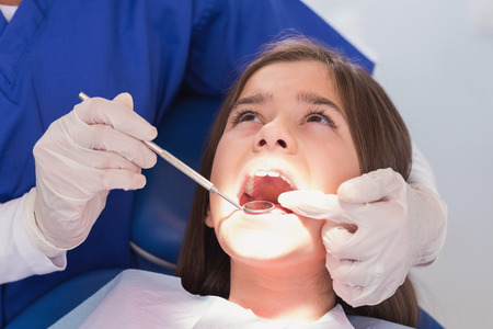 pediatric: Pediatric dentist examining her young patient in dental clinic